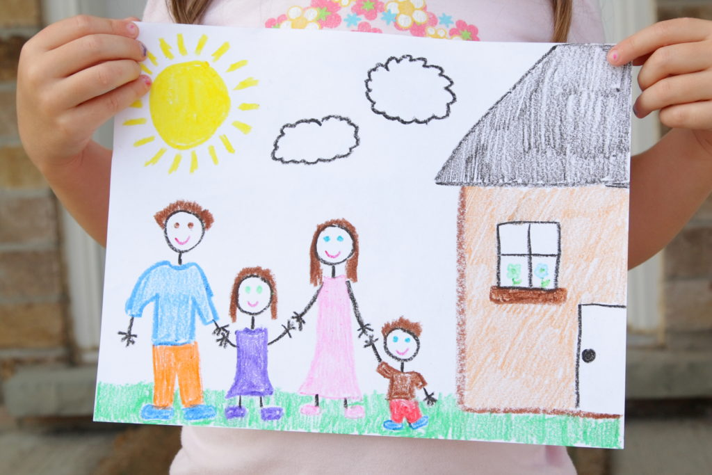 A four year old girl displays her drawing of her family standing outside of their beautiful new home.  The family includes a father, daughter, mother, and son all holding hands.  The drawing also includes a bright sun, clouds, and a house.